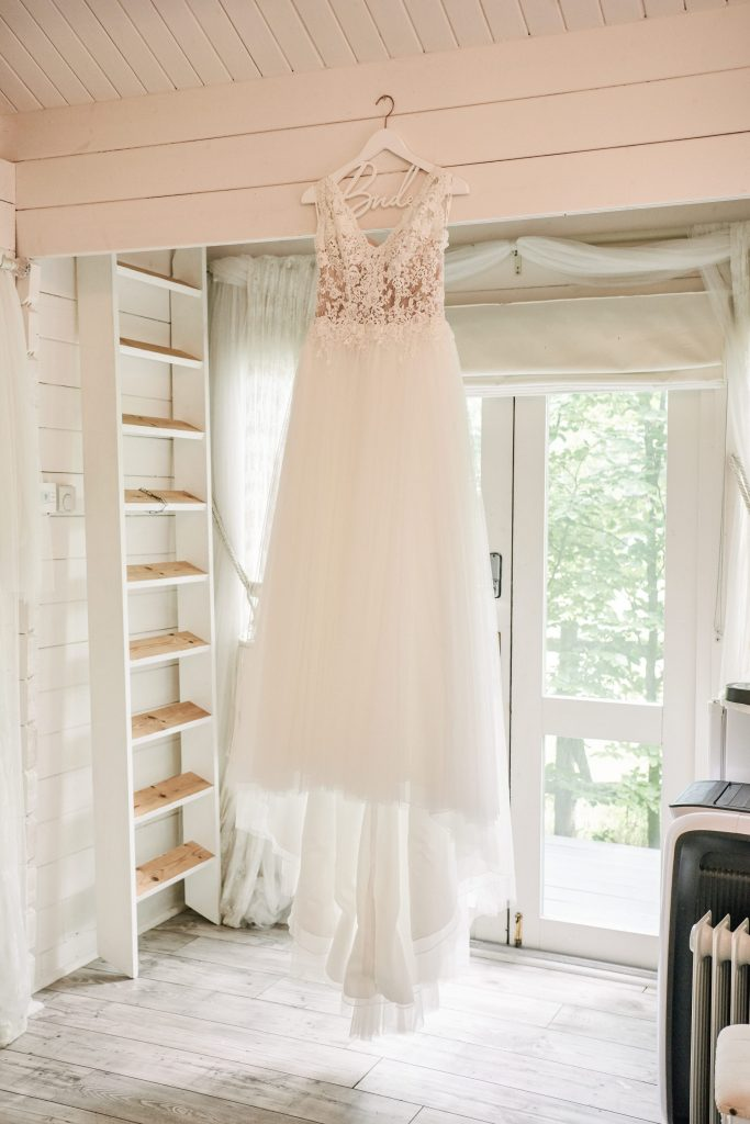 lace wedding dress hung up in white bridal room at Marleybrook House