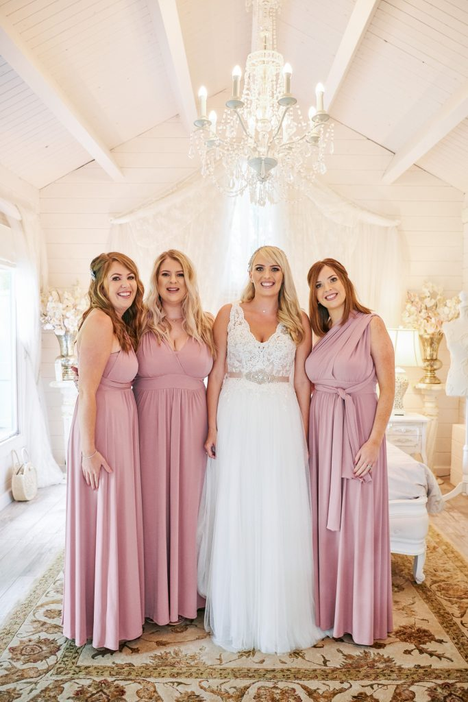 bride stood smiling with bridesmaids in bridal prep room at Marleybrook House