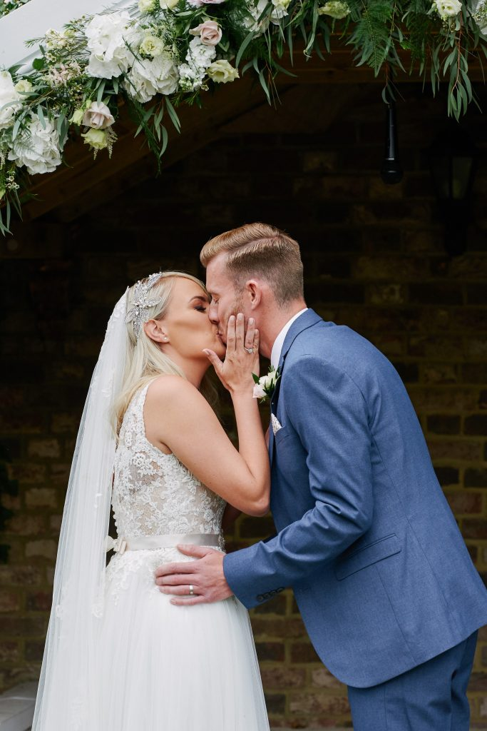Wedding couple kissing during outdoor ceremony at Marleybrook House