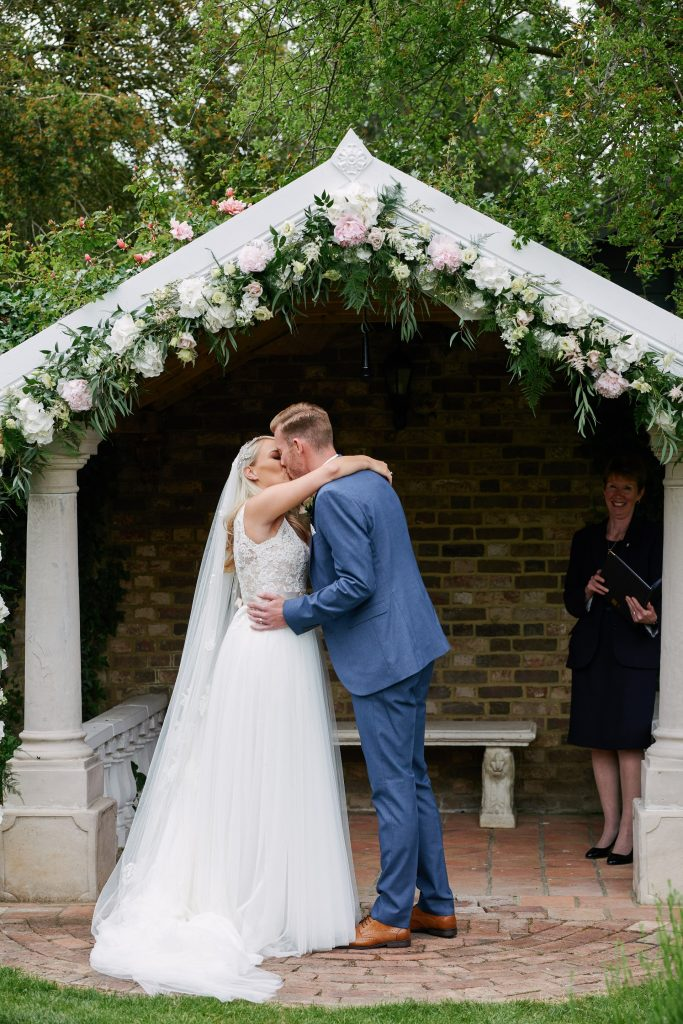 Bride and groom kissing during outdoor ceremony at Marleybrook House