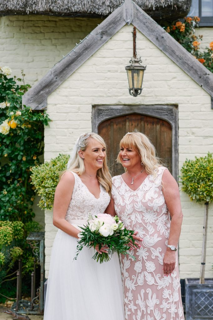 Bride with her mum in front of quaint english cottage at Marleybrook House