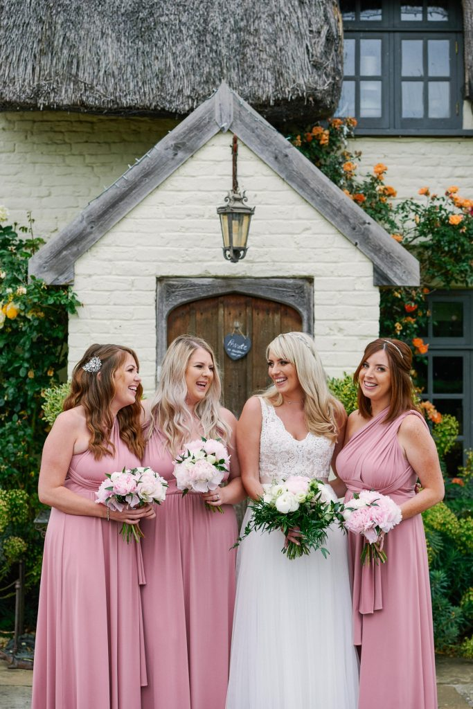 Bride with bridesmaids in front of quaint english cottage at Marleybrook House