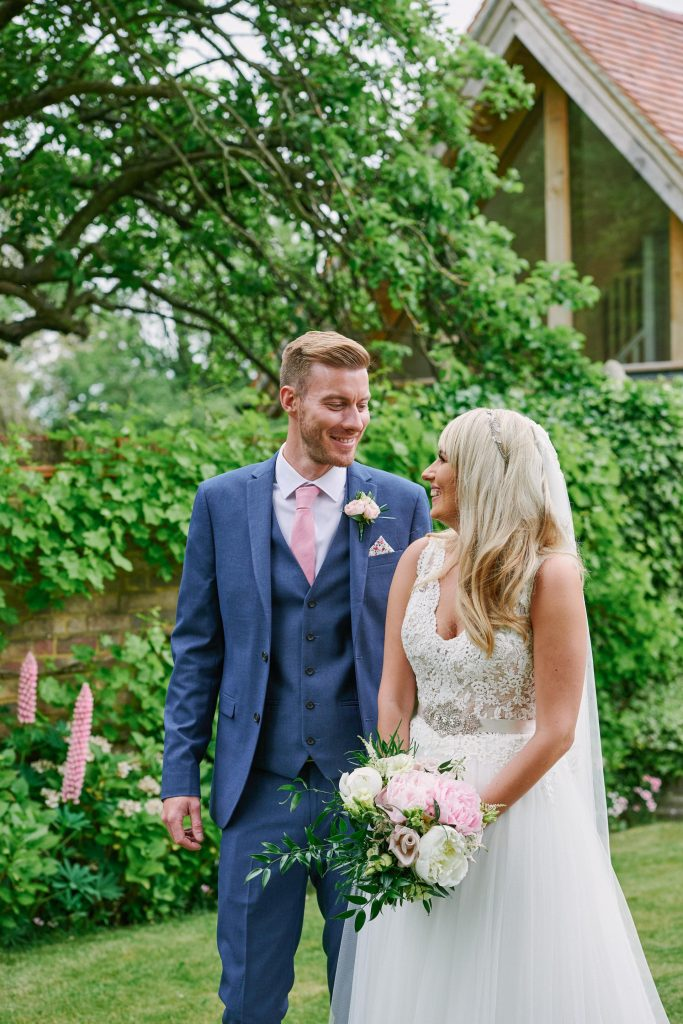 happy bride and groom laughing in the walled garden at Marleybrook House