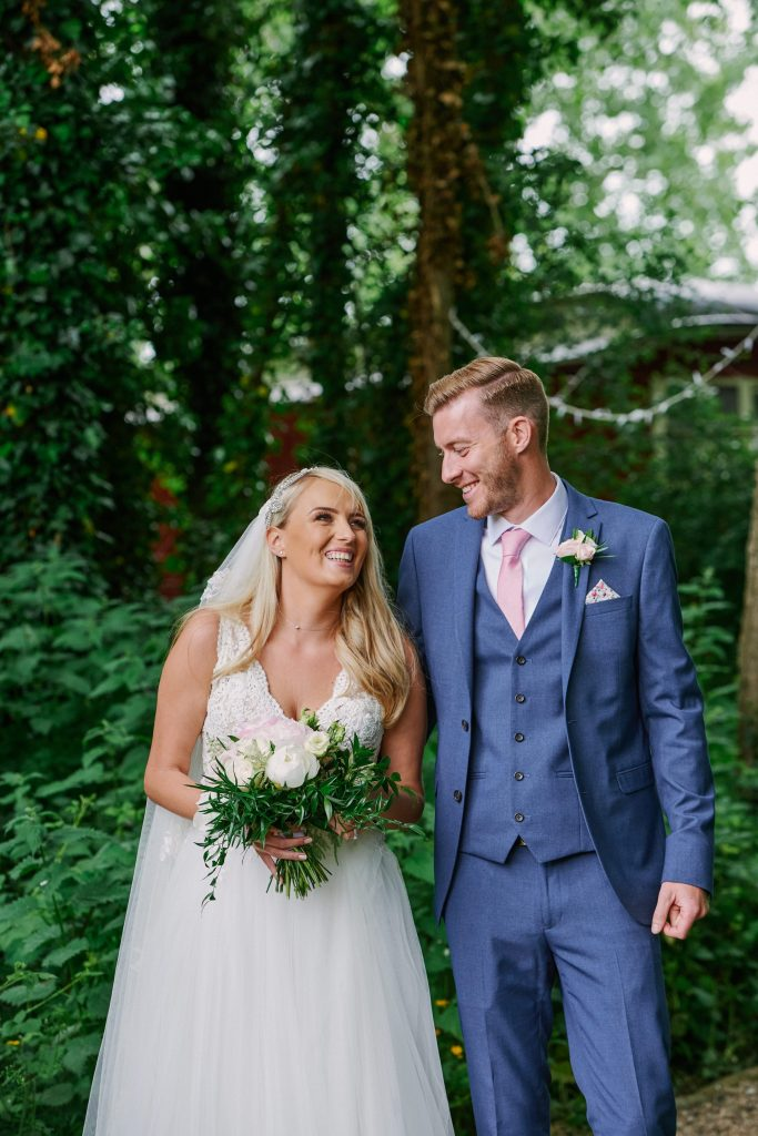 Wedding couple laughing together in woodland at Marleybrook House