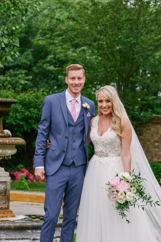 Bride and groom stood smiling together outside at Marleybrook House