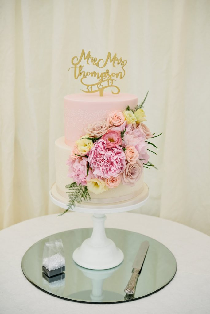 Pink and cream Wedding  cake with roses on a mirrored stand.