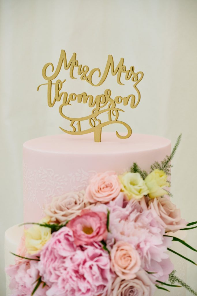 Pink Wedding  cake with roses on it and gold personalised lettering