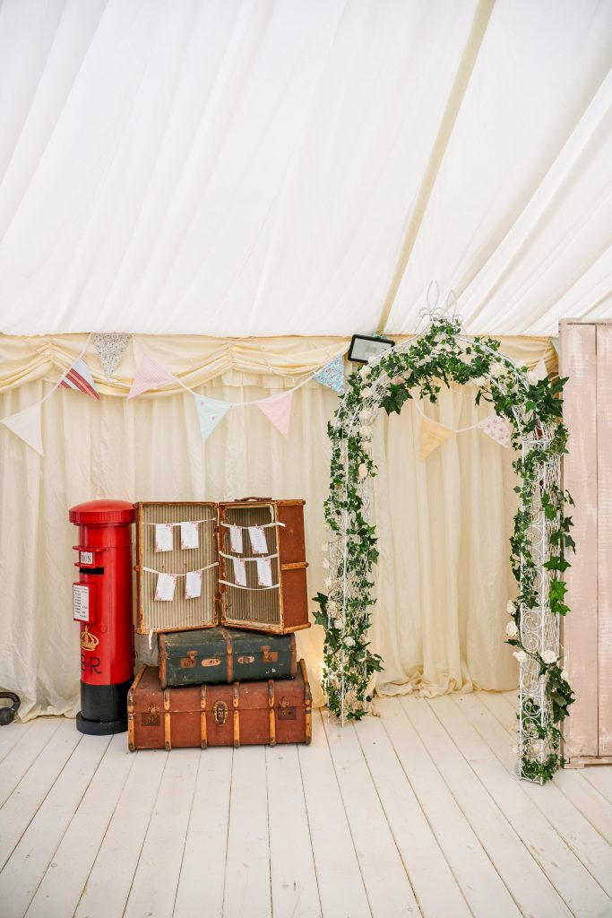 Wedding breakfast room details featuring red postbox and vintage suitcase table plan