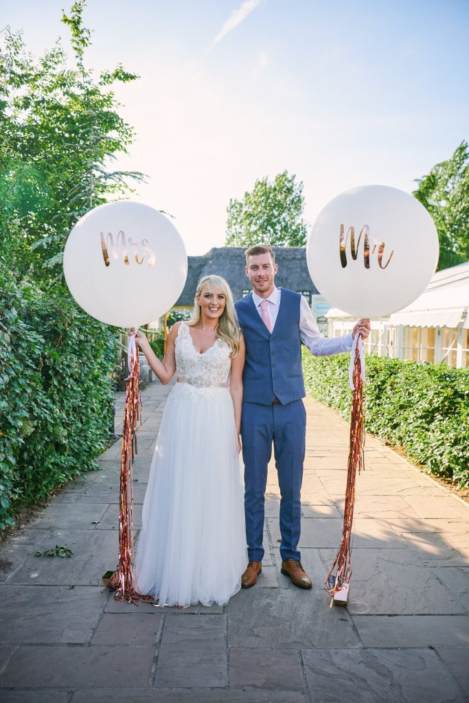 bride and groom holding mr and mrs balloons at Marleybrook House