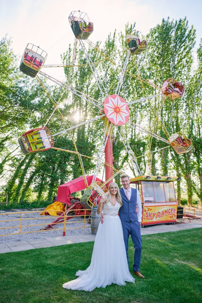 Bride and groom stood in front of a big wheel funfair ride at unique wedding venue.