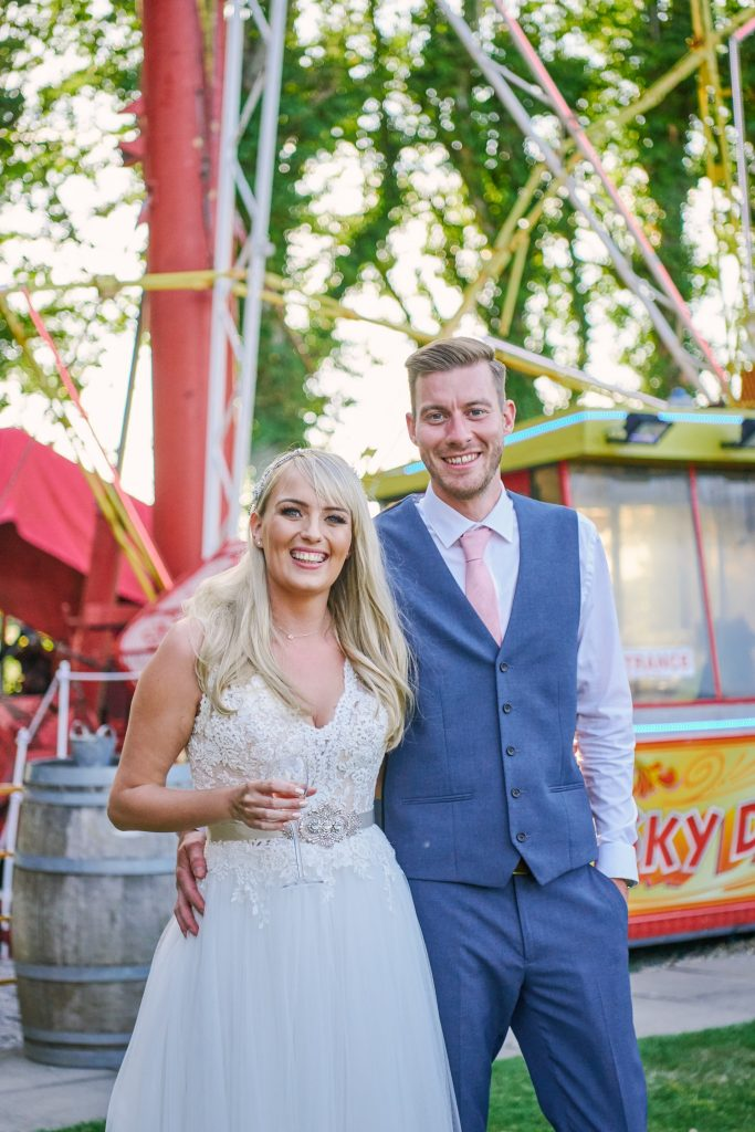 Bride and groom stood in front of vintage funfair ride