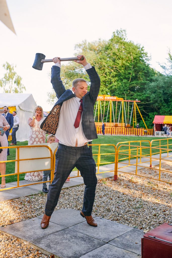 wedding guest playing on strongman fairground game at unique outdoor wedding