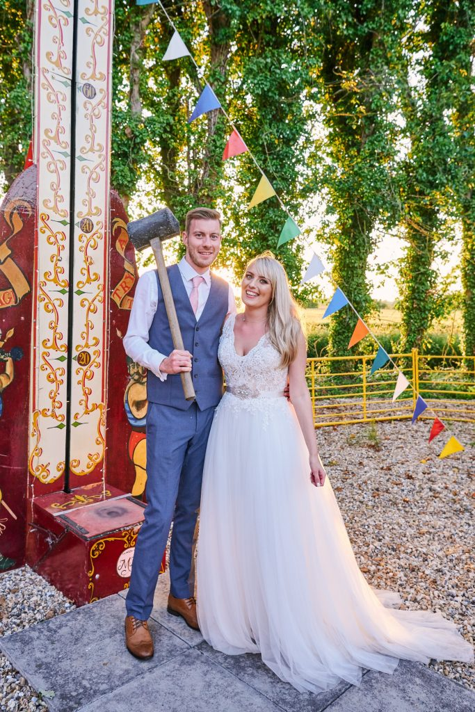 Wedding couple posing with strongman hammer at unique vintage funfair venue