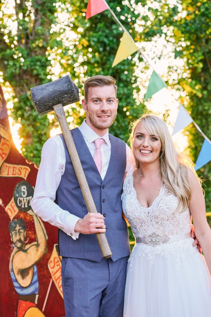 Happy wedding couple with hammer at unique vintage funfair venue