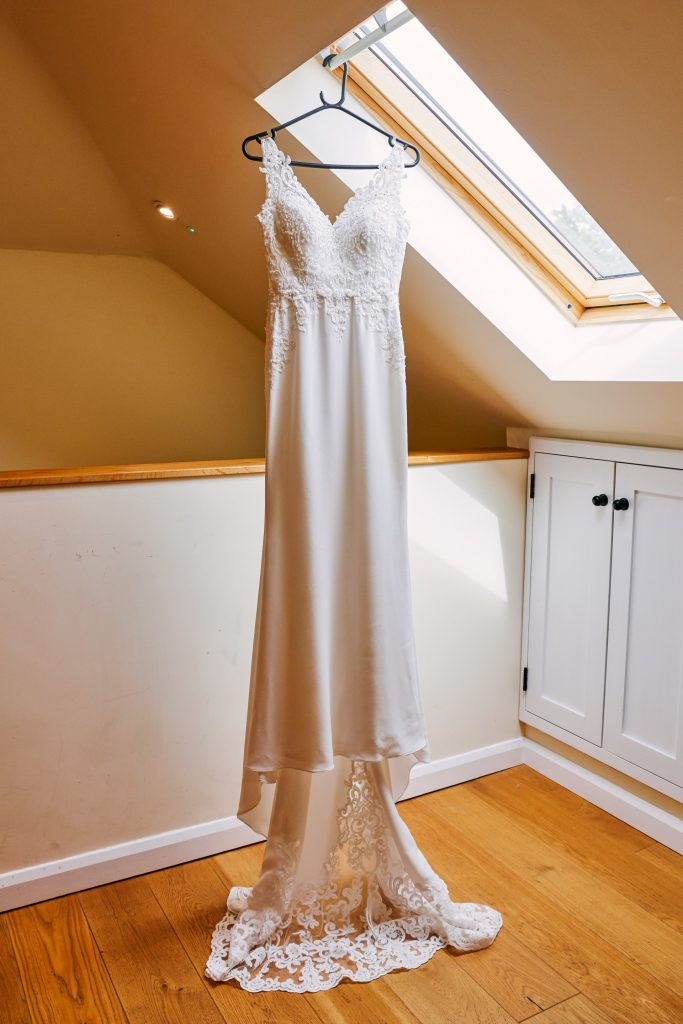 Wedding dress hung up in a barn room at Micklefield Hall