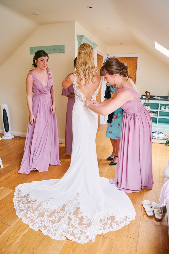 Bridesmaids helping to button up brides beautiful white lace dress