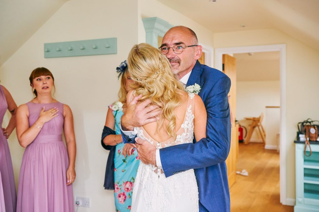 Father of the bride hugging his daughter during bridal preparations
