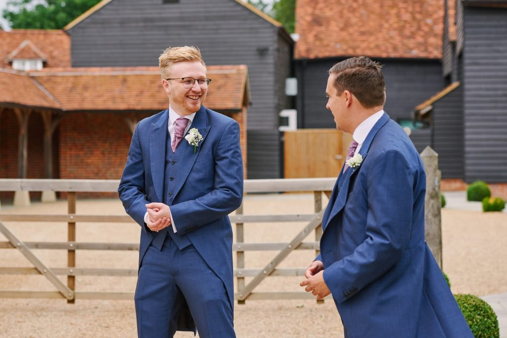 Ushers laughing whilst stood outside of the barn entrance at Micklefield Hall