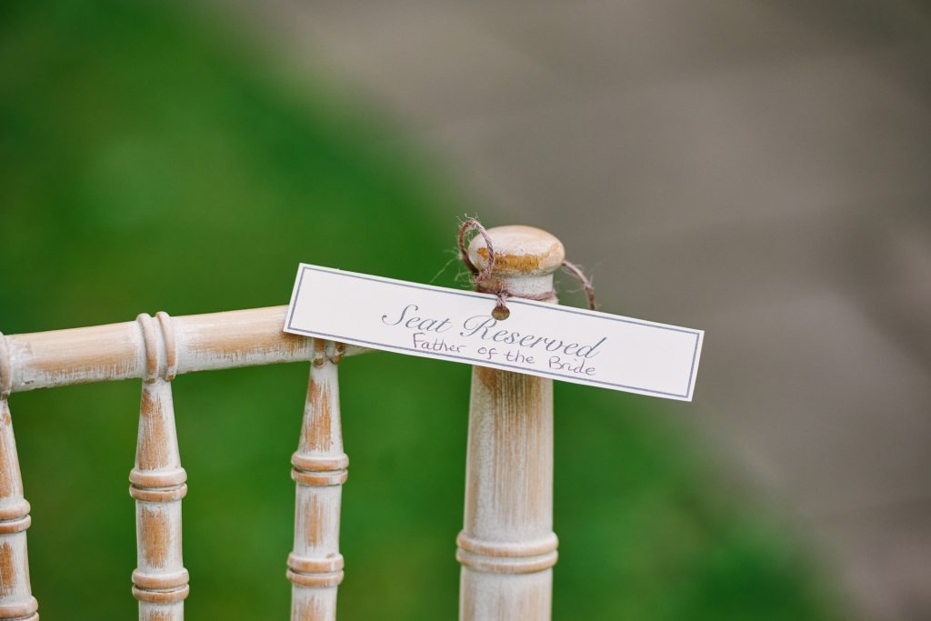 Seat reserved sign on rustic wooden ceremony chairs