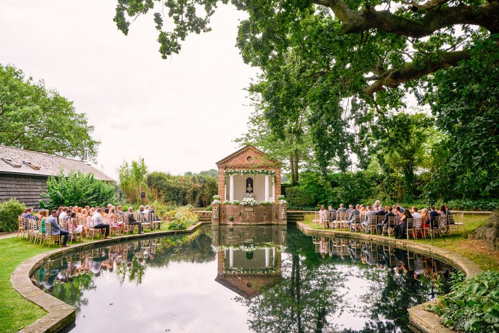 Beautiful outdoor garden wedding ceremony set up surrounding a pond
