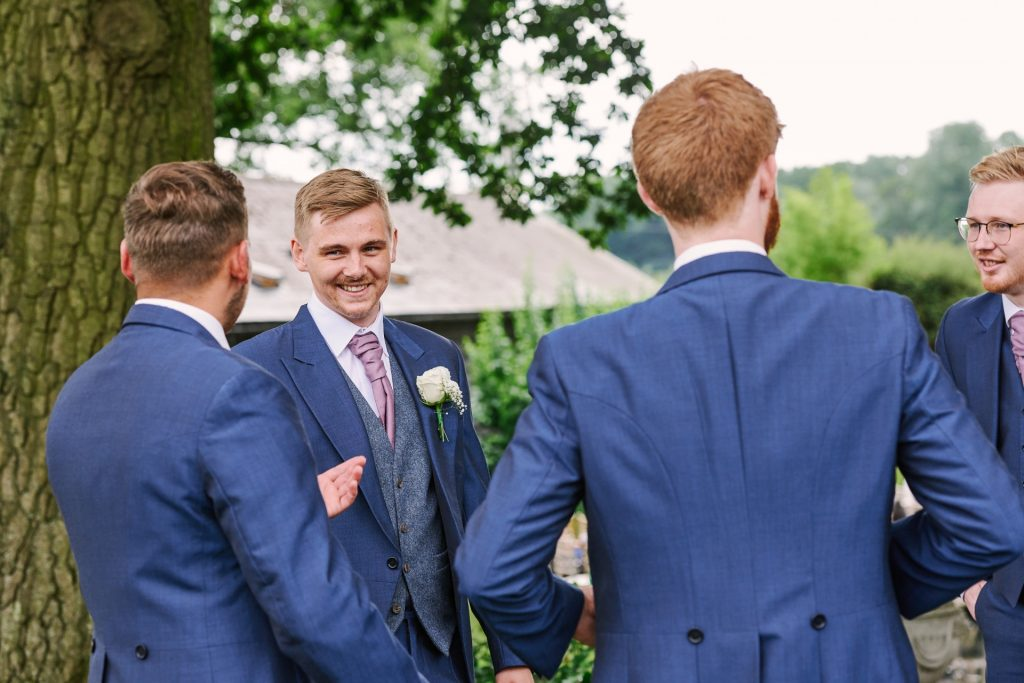 Groom laughing with his ushers before wedding ceremony