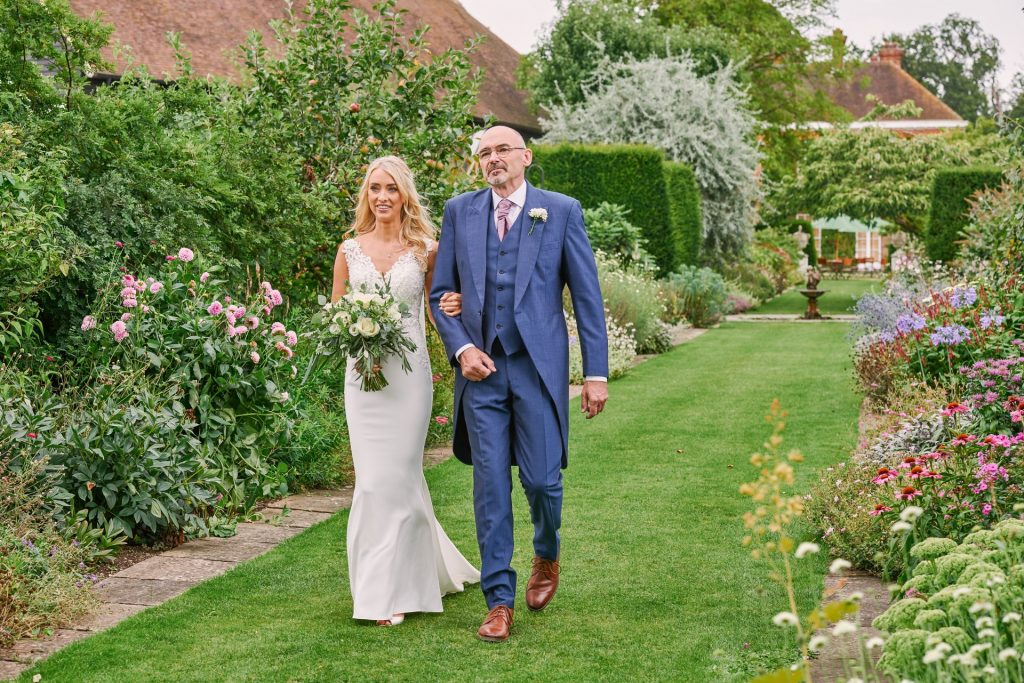 Beautiful bride walking down the outdoor aisle with her dad at Micklefield Hall