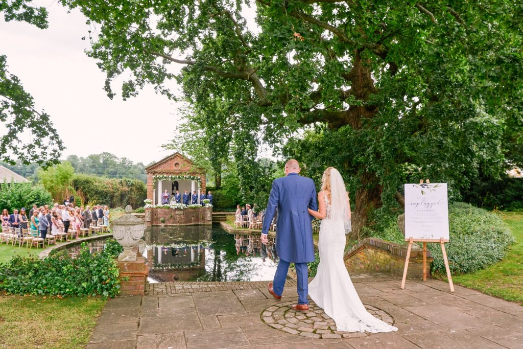 Bride and her father walking into beautiful outdoor garden ceremony