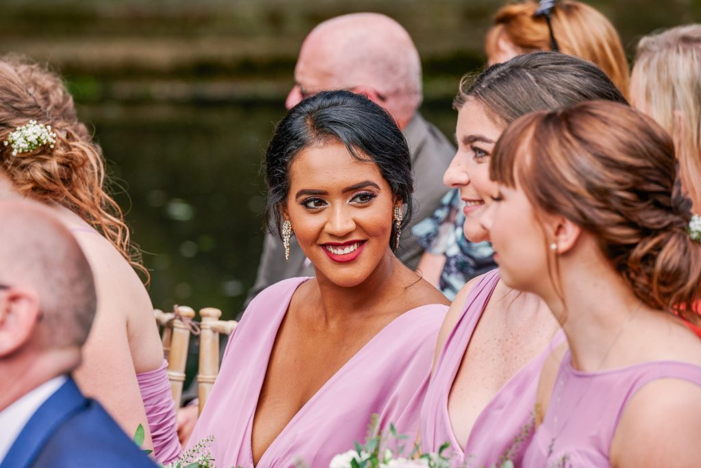 Happy bridesmaid smiling during outdoor garden wedding at Micklefield Hall