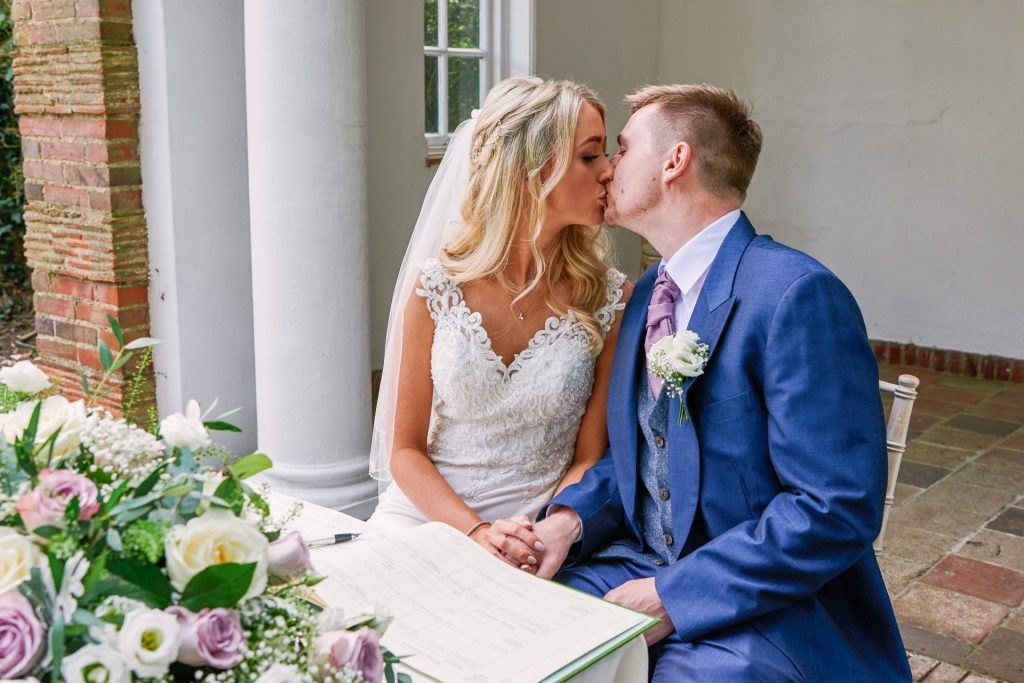 Bride and groom kissing during beautiful outdoor garden wedding at Micklefield Hall