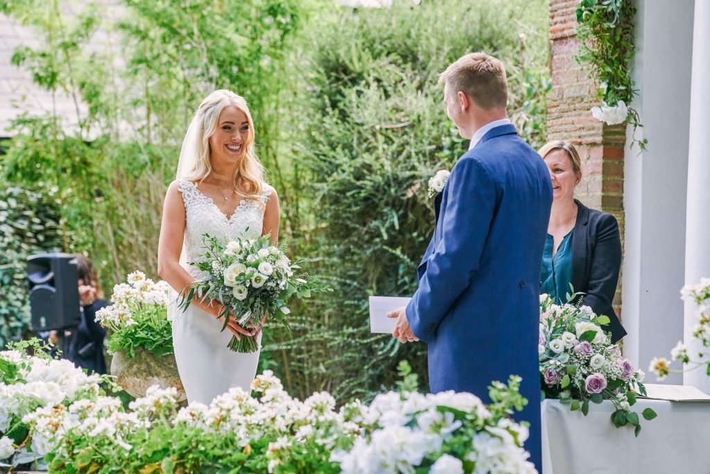 Bride smiling whilst walking up to her groom during beautiful outdoor garden wedding