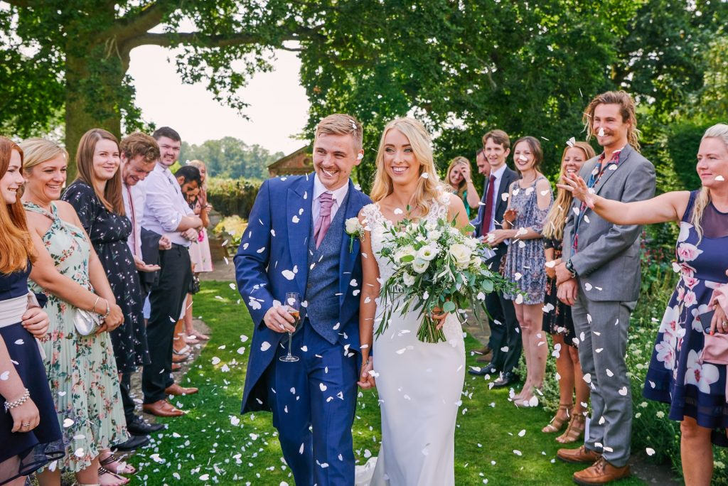 Bride and groom walking through confetti during beautiful outdoor garden wedding