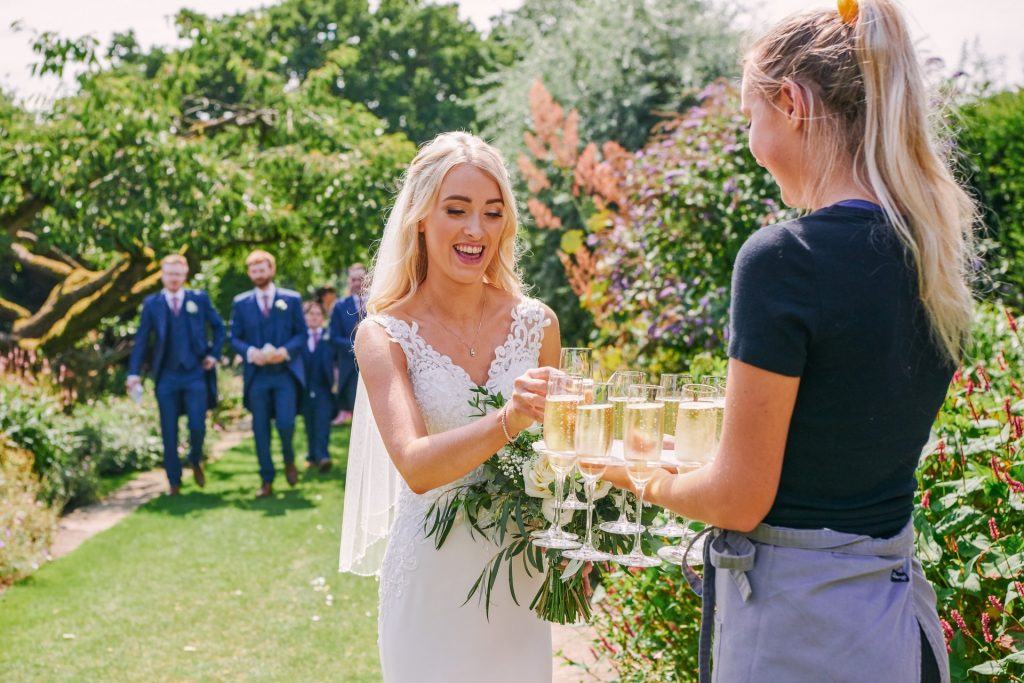 Bride taking a glass of champagne during beautiful summer wedding in the gardens at Micklefield Hall