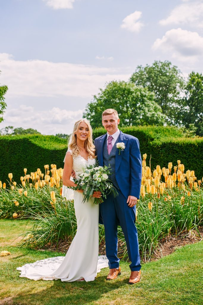 Bride and groom in front of yellow flowers in the gardens at Micklefield Hall