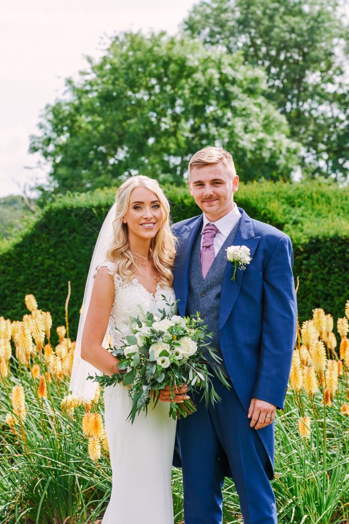 Bride and groom stood in front of yellow flowers on a beautiful sunny day
