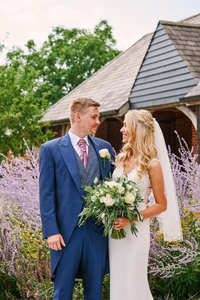 Bride and groom stood outside in front of beautiful lavender plants