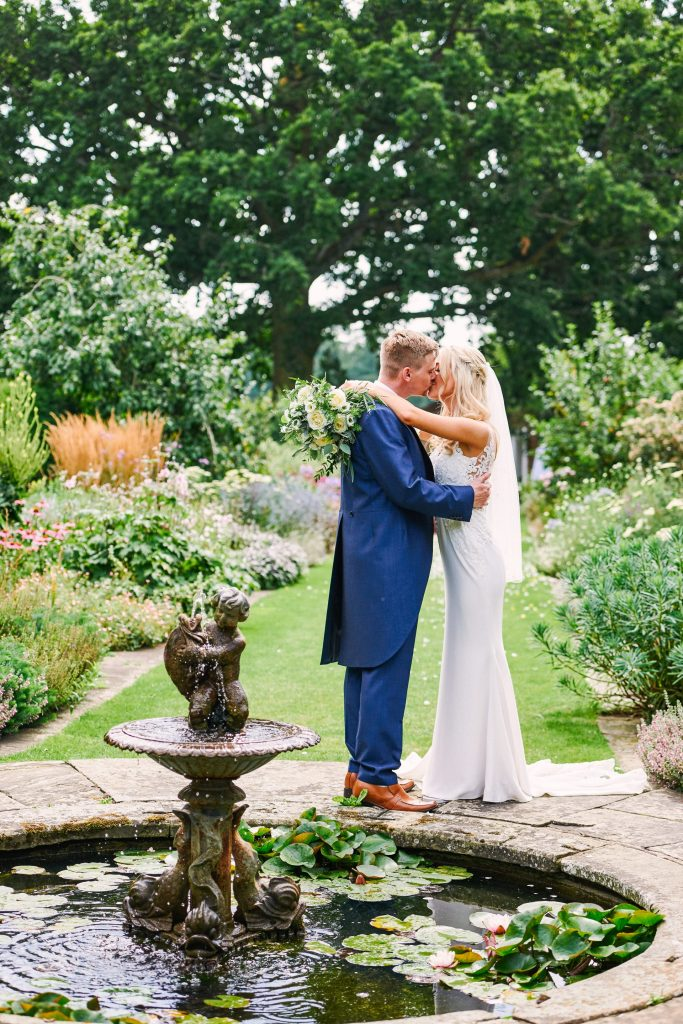 Wedding couple kissing in front of a fountain in beautiful country garden