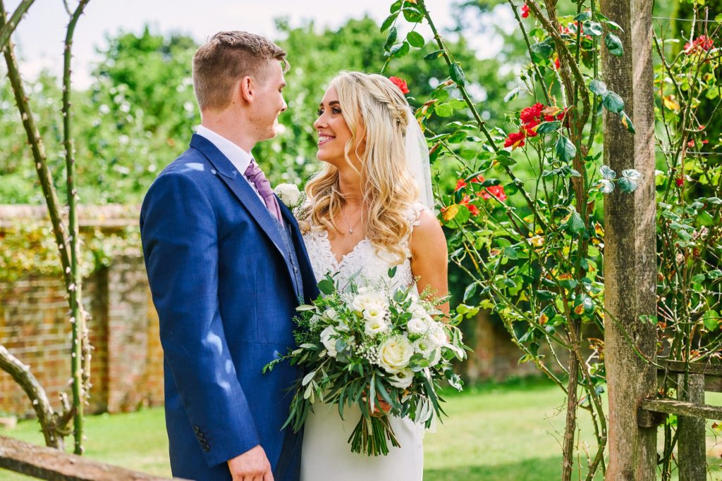 Bride and groom stood outdoors in a beautiful rose garden at Micklefield Hall