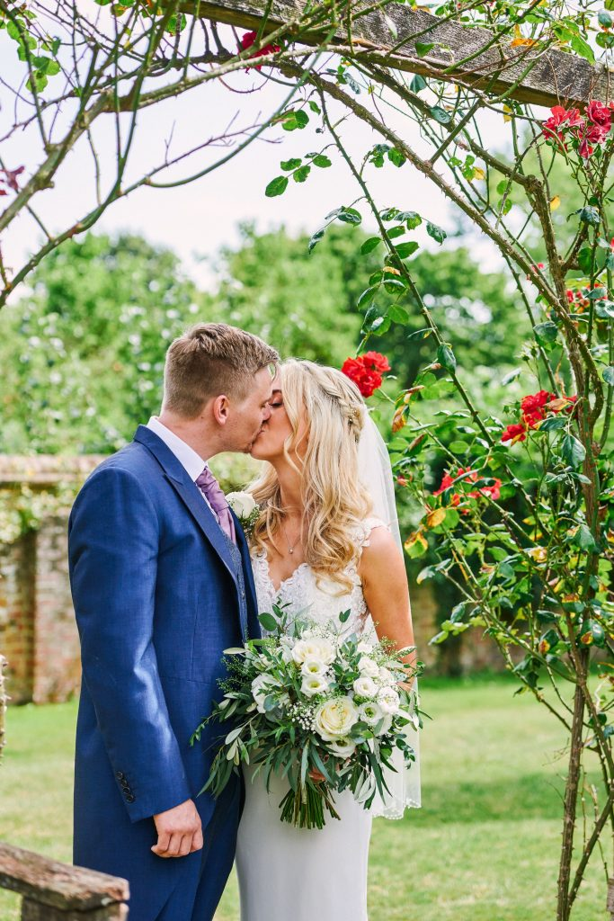 Happy bride and groom kissing outside in a beautiful rose garden