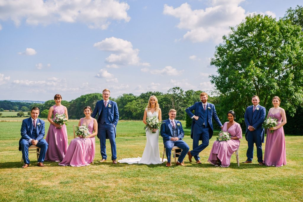 creative outdoor bridal party group shot with some people sat and some stood