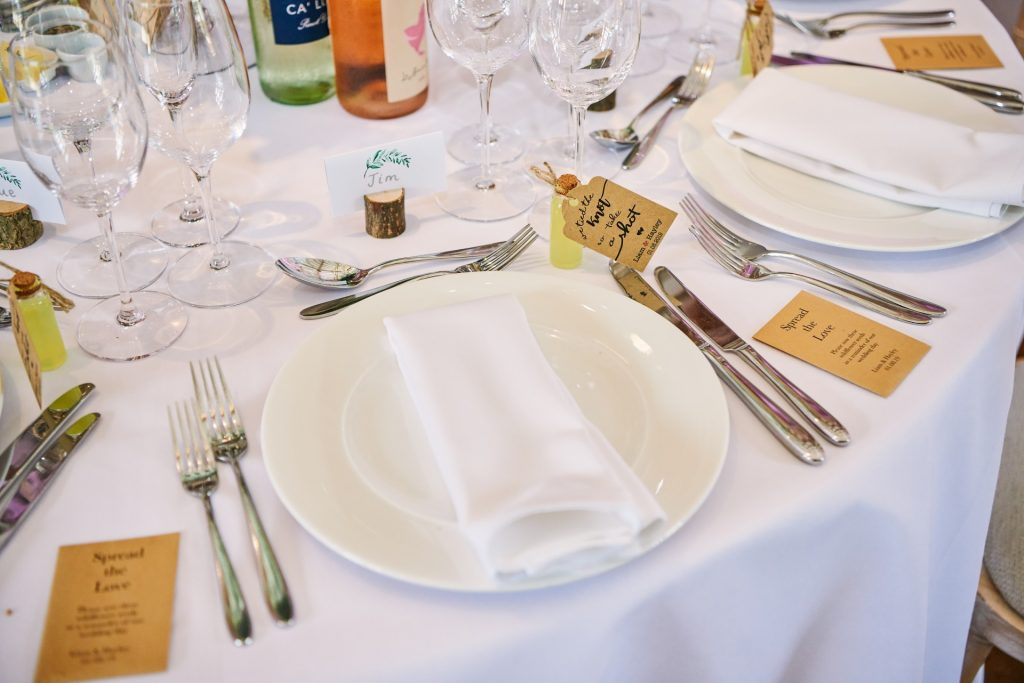 Wedding breakfast table details with alcohol bottle favours and wooden name places