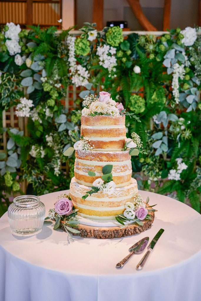 Beautiful layered sponge wedding cake in front of floral background at Micklefield Hall