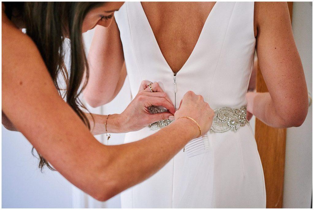 bride having her wedding dress done up