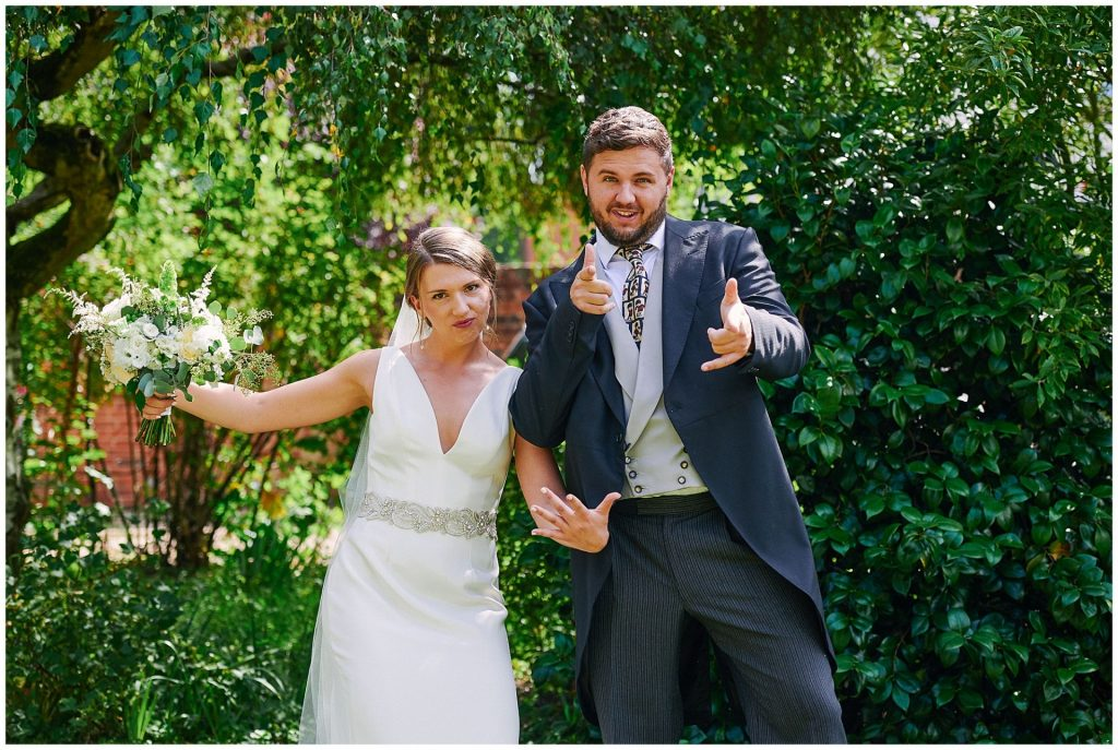 Bride and her brother pulling a silly pose in their sunny garden