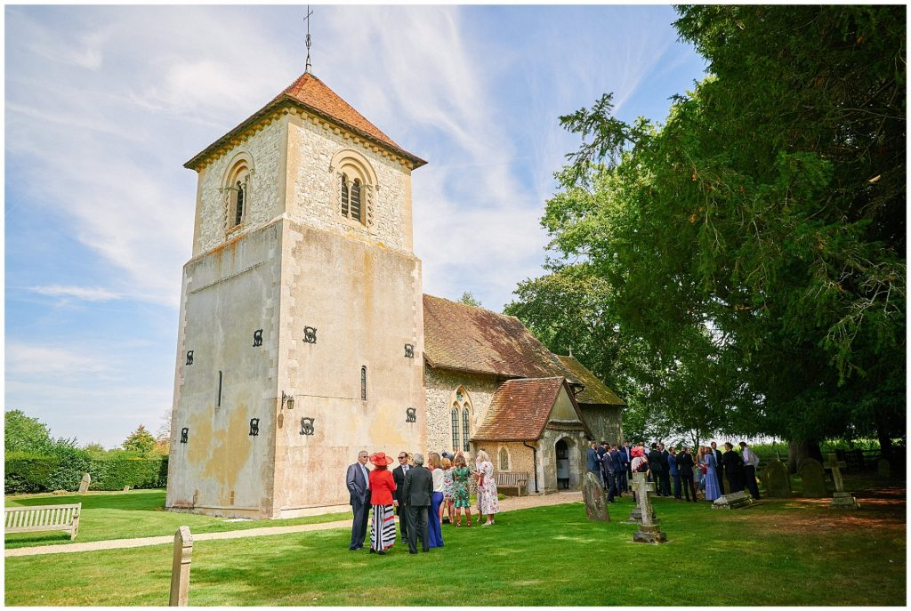 Wedding guests gathering outside of church venue on a sunny day in reading