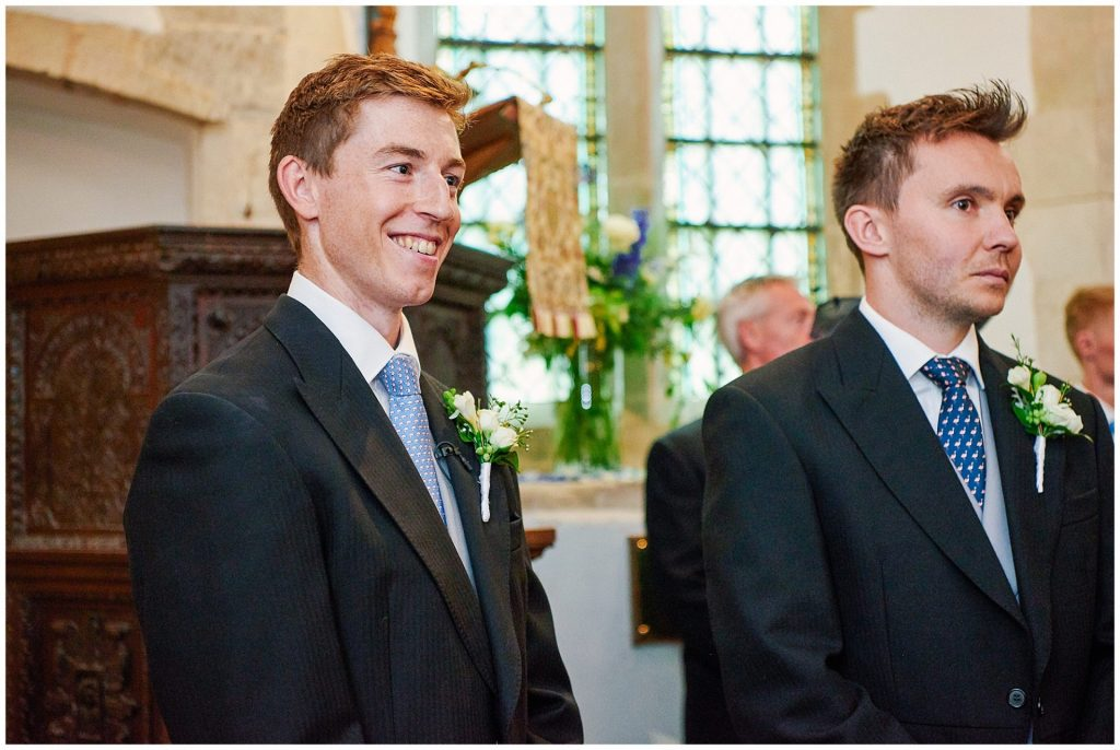 Groom smiling whilst waiting at the alter