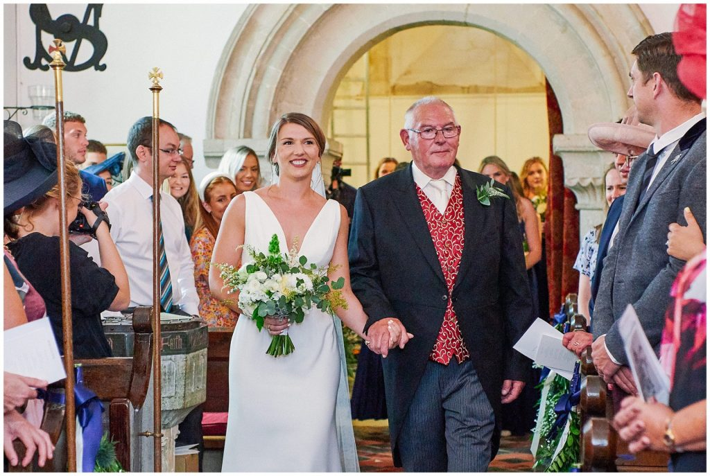 bride smiling and walking up the isle with her father