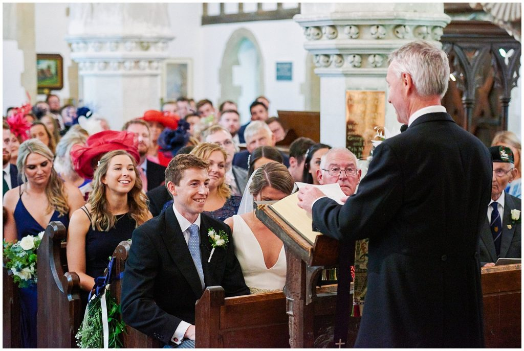father of the groom reading a speech whilst happy wedding guests watch