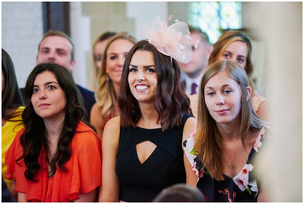 Wedding guest smiling during wedding ceremony