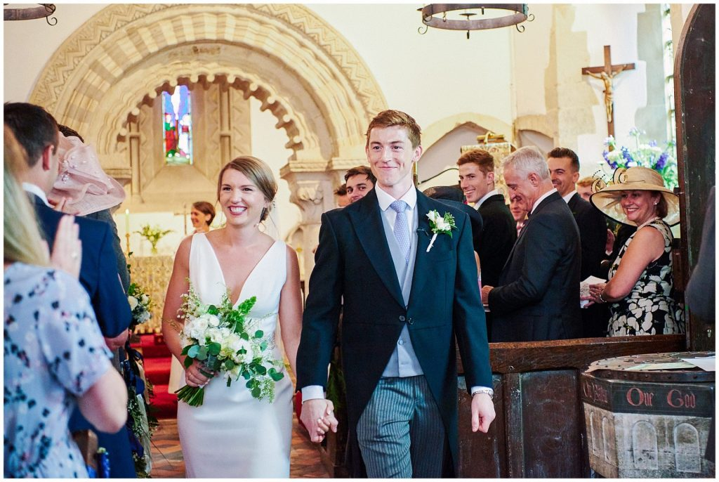 Bride and groom smiling as they are walking out of their wedding ceremony