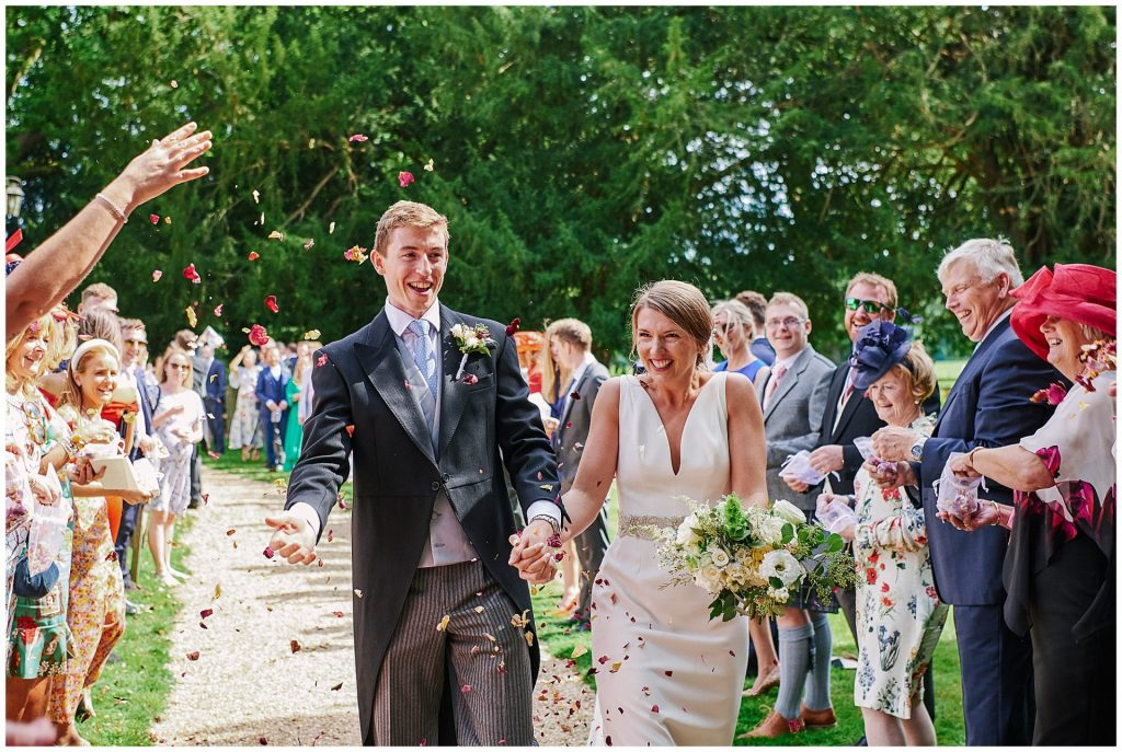 bride and groom smiling as wedding guests throw confetti at them
